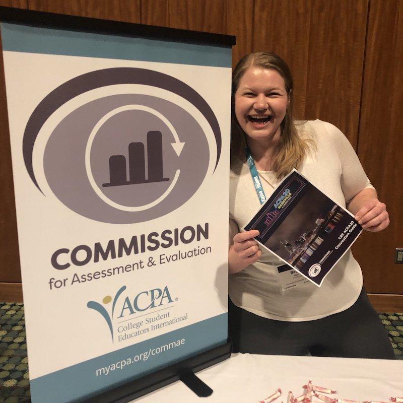 Commission for Assessment & Evaluation smiling member holding a flyer