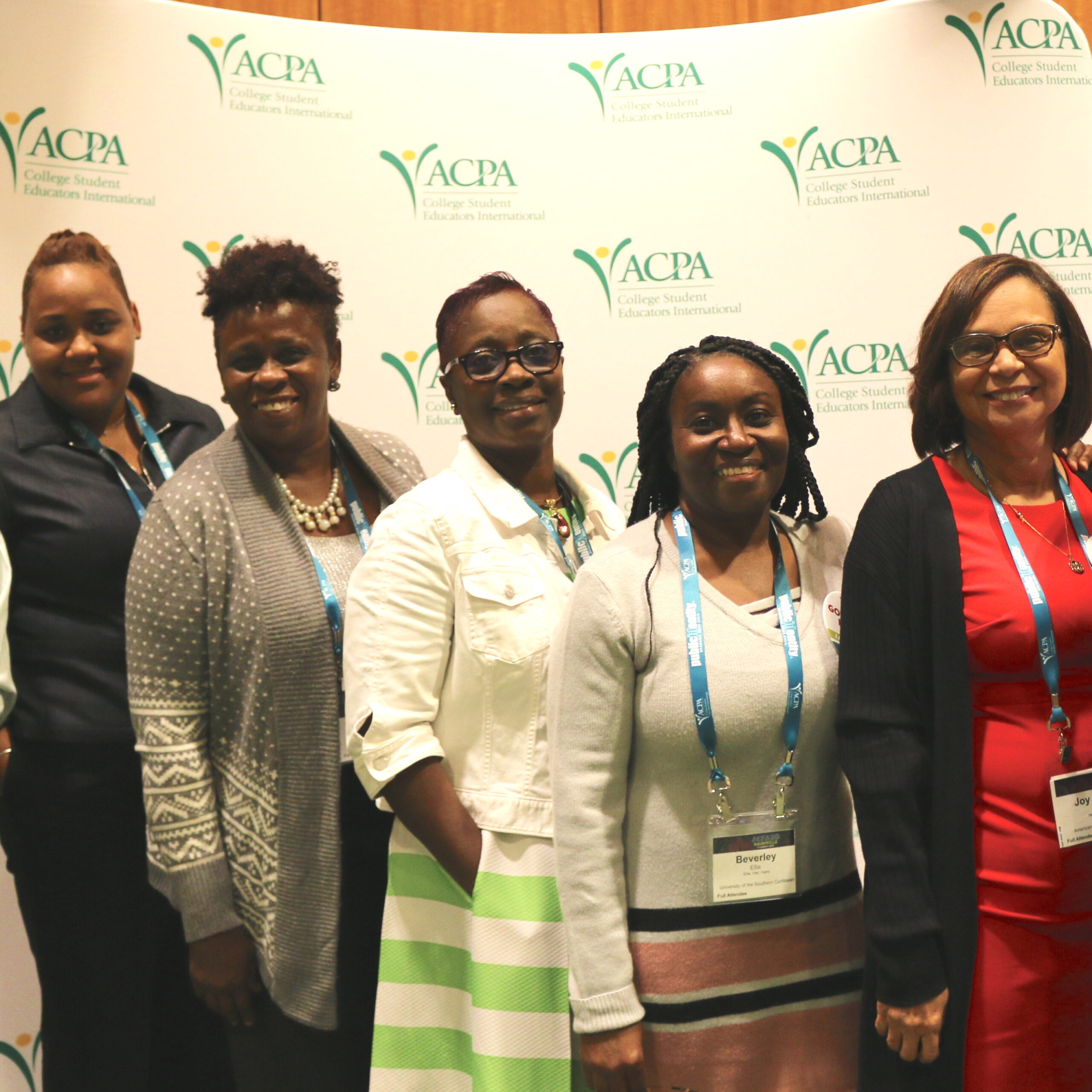 5 Caribbean Tertiary International Division members posing for a photo in front of the ACPA logo
