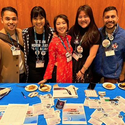 5 APAN leaders standing at a table during ACPA20 handing out buttons and flyers