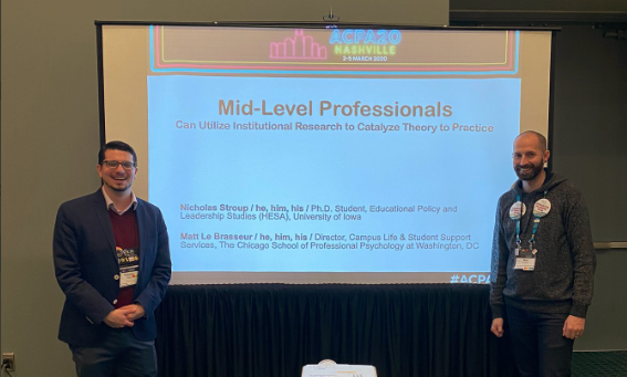 Two mid-level professionals standing in front of a projector screen smiling before a presentation