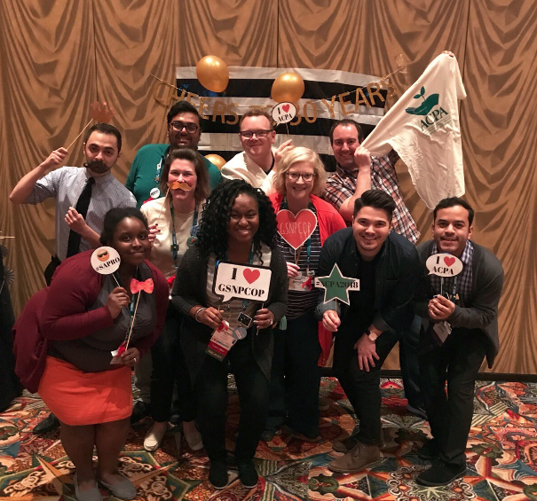 a large group of Graduate Student and New Professional Community of Practice members holding photobooth signs and smiling for a group photo