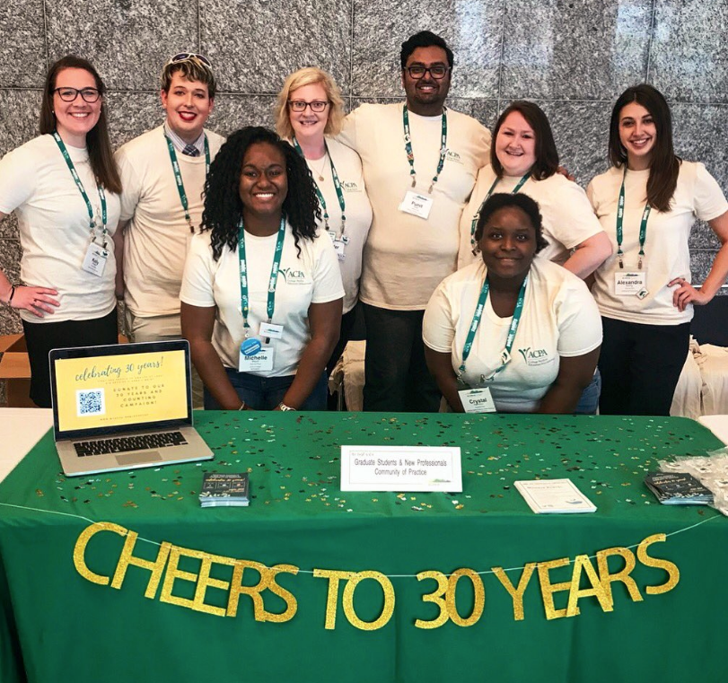 Graduate Students and New Professionals Community of Practice standing behind a table that reads CHEERS TO 30 YEARS and smiling for a photo