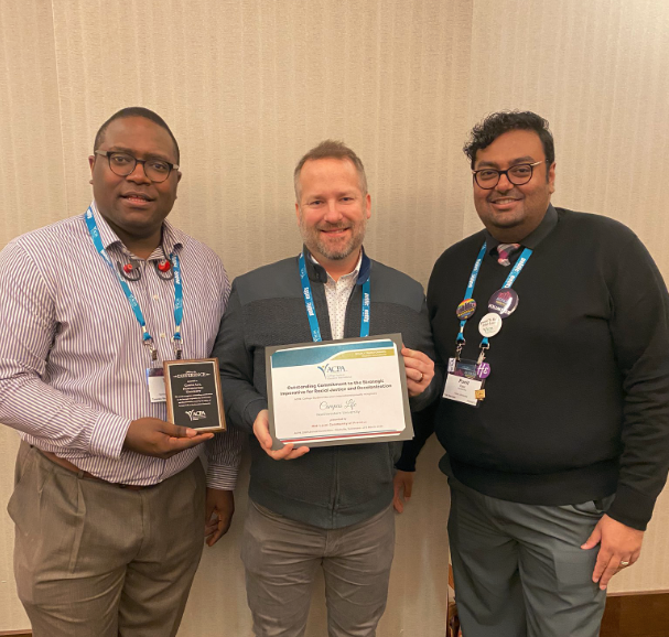 three male Mid Level Community of Practice ACPA members holding two Awards and smiling for the camera
