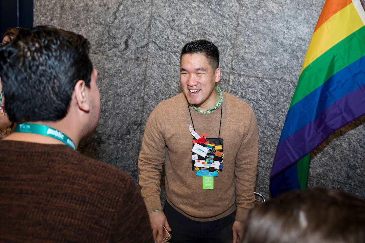 CSGI leader smiling at a new member with a rainbow flag to the right