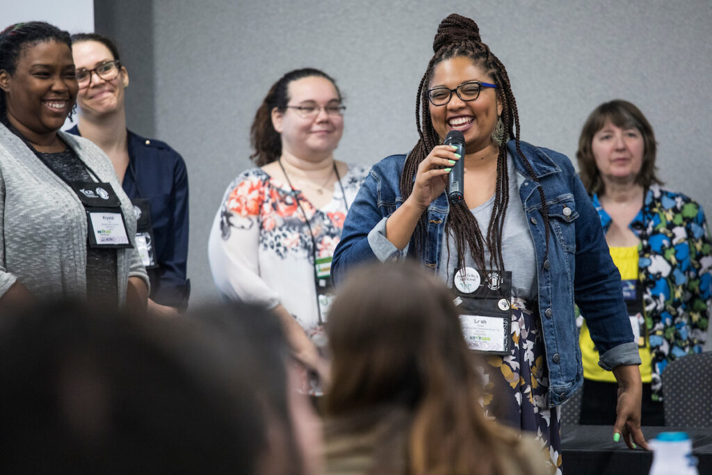 student at the nextgen institute holding a microphone surrounded by other participants with smiling faces