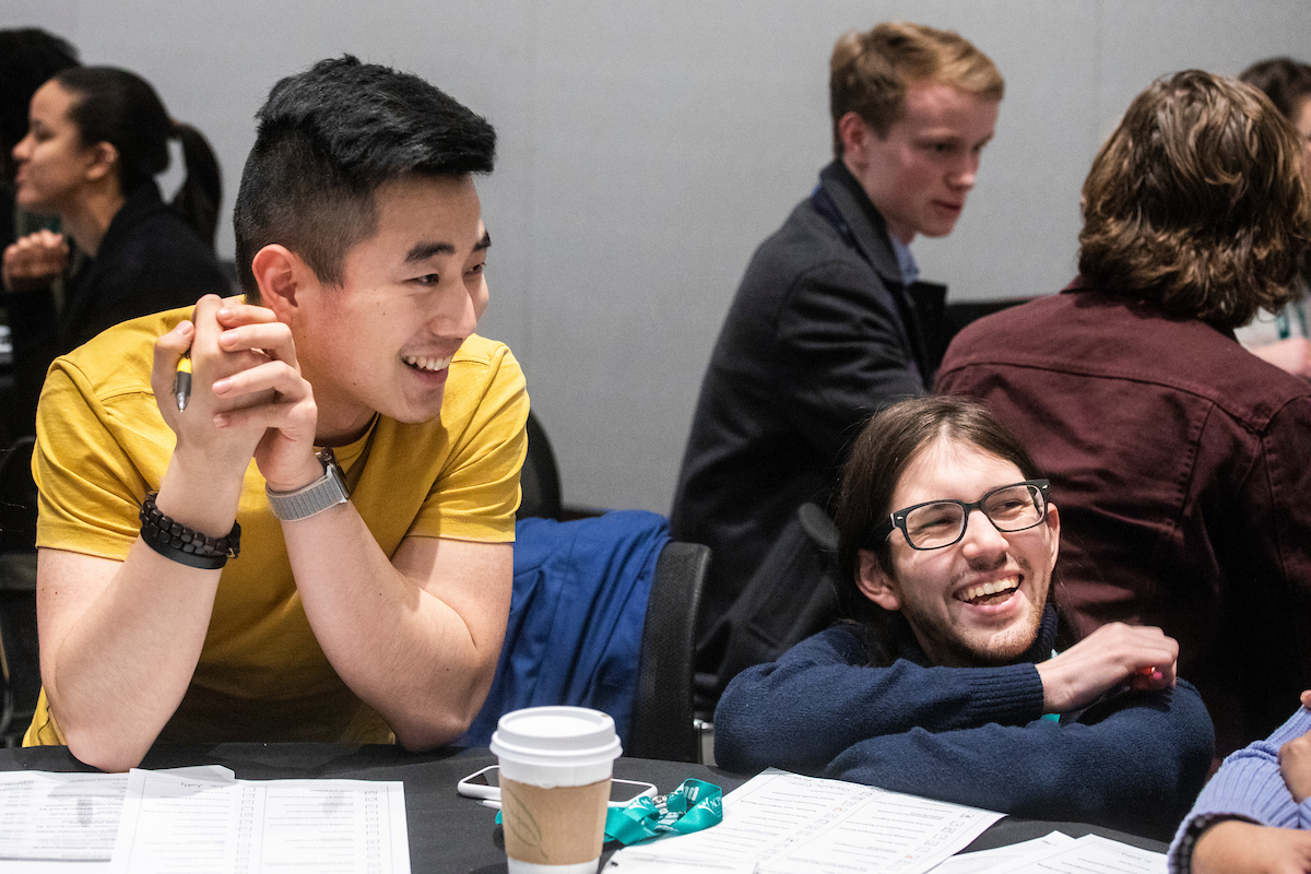 two students at the NextGen Institute smiling while sitting around a table